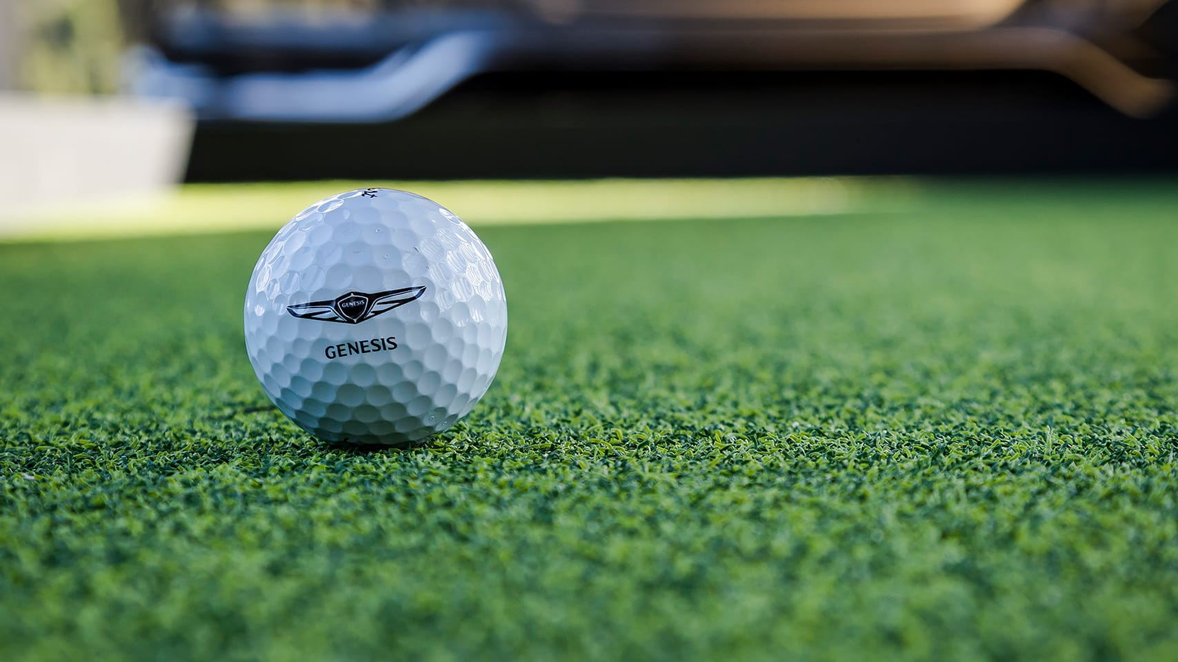 Golf ball with Genesis logo on green turf.